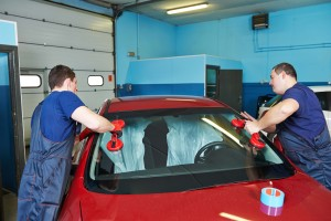 Vehicleglazier adding glue on to the windscreen or windshield of a car in an auto service station garage before installation